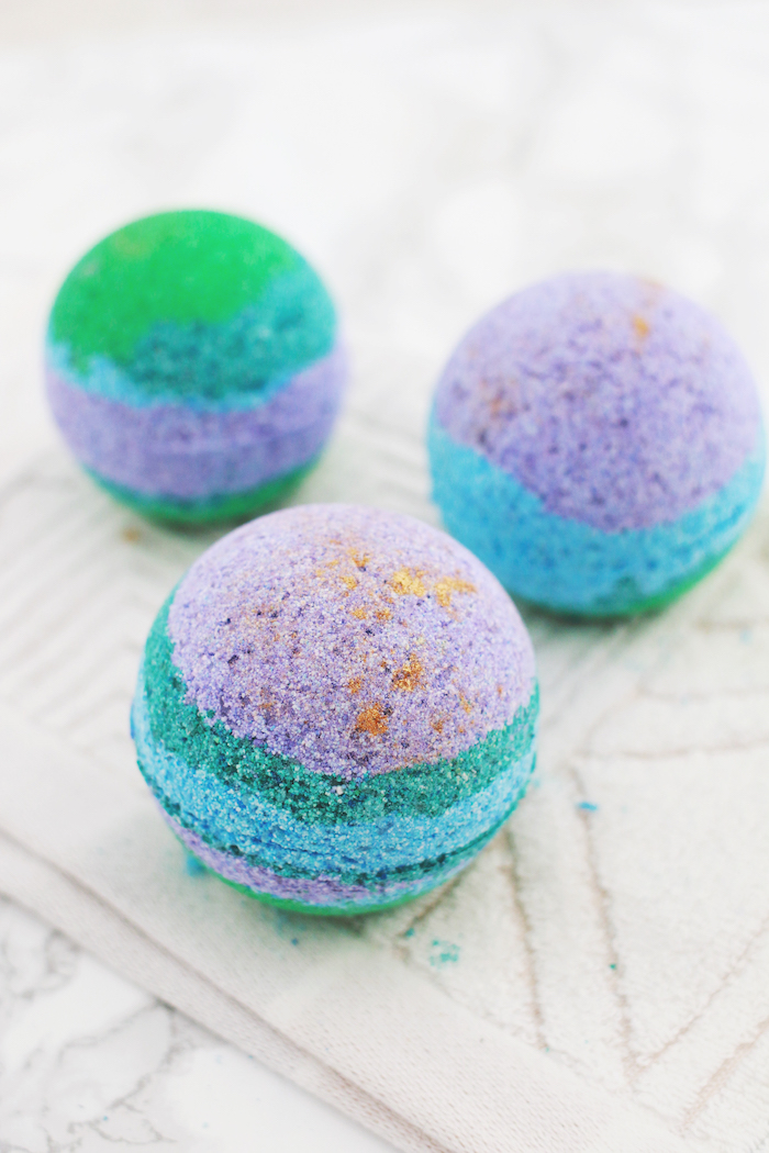 how to use a bath bomb, three spherical striped bath bombs, in green and violet, teal and orange, placed on a textured cream fabric