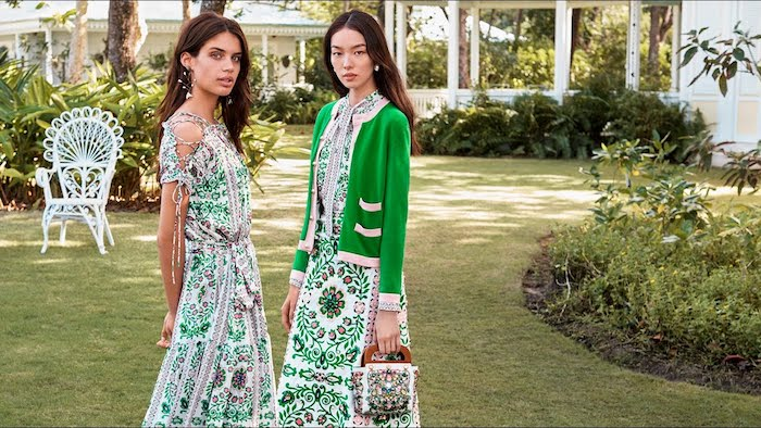 two young brunette women, wearing maxi dresses in green and white, decorated with floral patterns, and other colors, what is semi formal, green and pink cardigan, and small retro bag