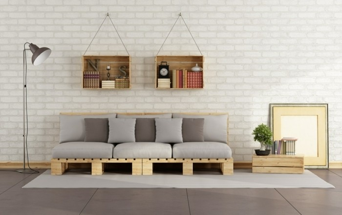 two wooden bookshelves, hanging on a white brick wall, above a couch made of light wooden pallets, and covered with cushions, in light and dark grey