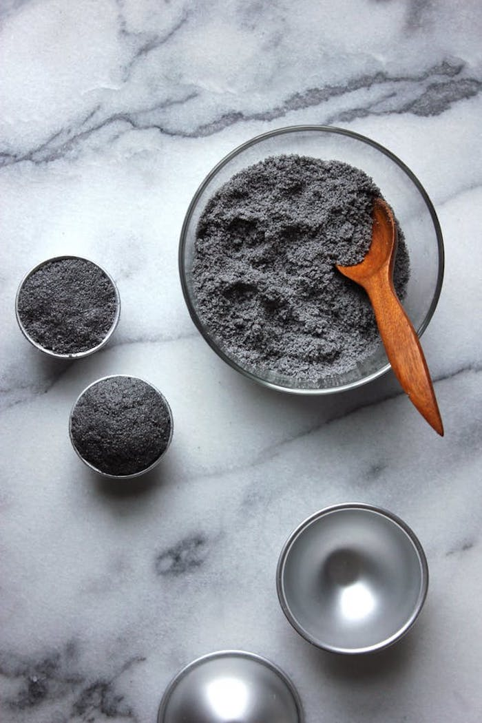 the process of making a dark grey or black bath bomb, mixing dark grey powder in a clear glass bowl, using a wooden spoon, filling a metal moulding dish with powder