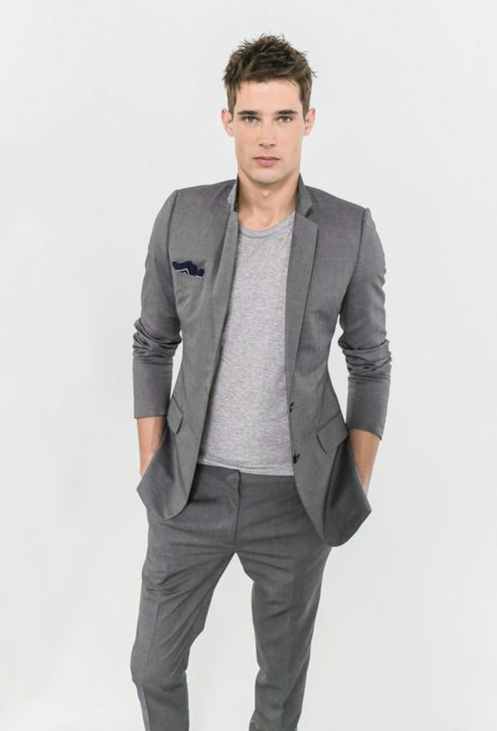 t-shirt in pale grey, worn with a dark grey suit, by young man, with hands in his jacket pockets, mens casual summer wedding attire, plain white background