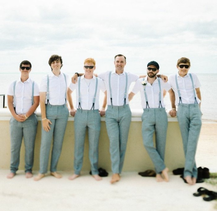 six men standing barefoot, and wearing grey trousers, white shirts and suspenders, mens casual summer wedding attire, sea in the background