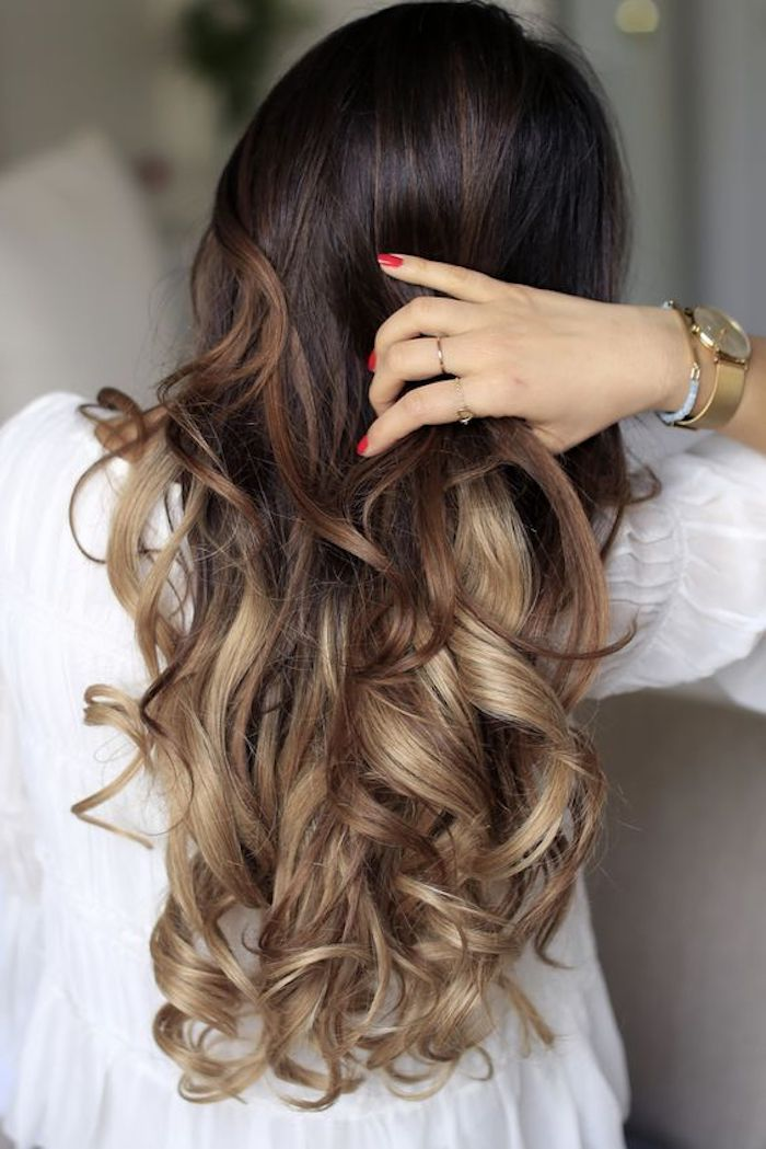 red nail polish, on hand holding a strand of long hair, ombre effect with dark brown top, and caramel highlights at the bottom