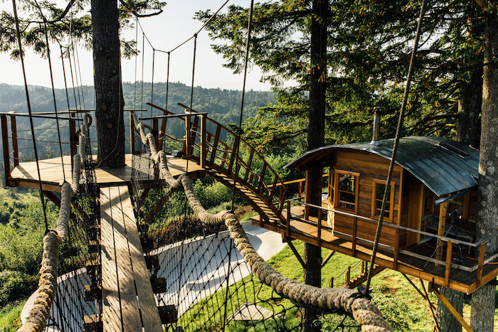 rope and wooden bridges, connecting several constructions, suspended above the ground, wooden tree house