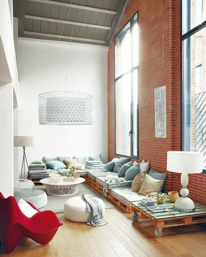 industrial style room, with high ceilings and two large windows, containing furniture made from pallets, a modern red armchair, and other items