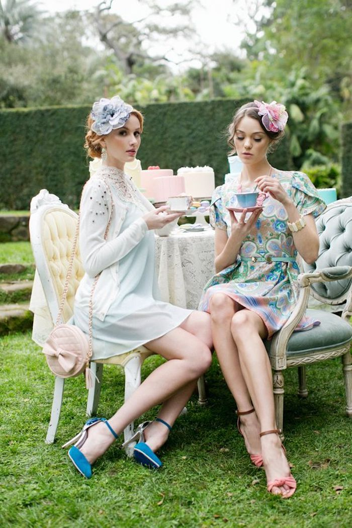semi formal dress code, two young women, having tea in a garden, wearing silky mini dresses, in pastel colors, with matching shoes, and hair ornaments