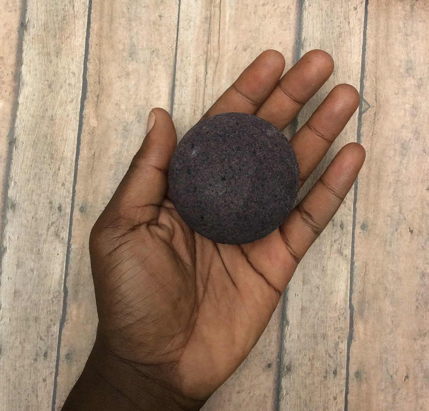 terxtured black bath bomb, in the palm of a person's hand, old worn wooden surface in the background