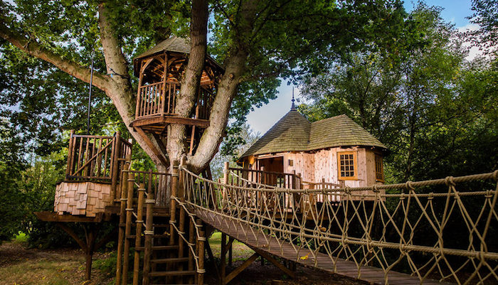 gazebo and a small house, built on green trees, using wood and other materials, and connected by several bridges and stairs,