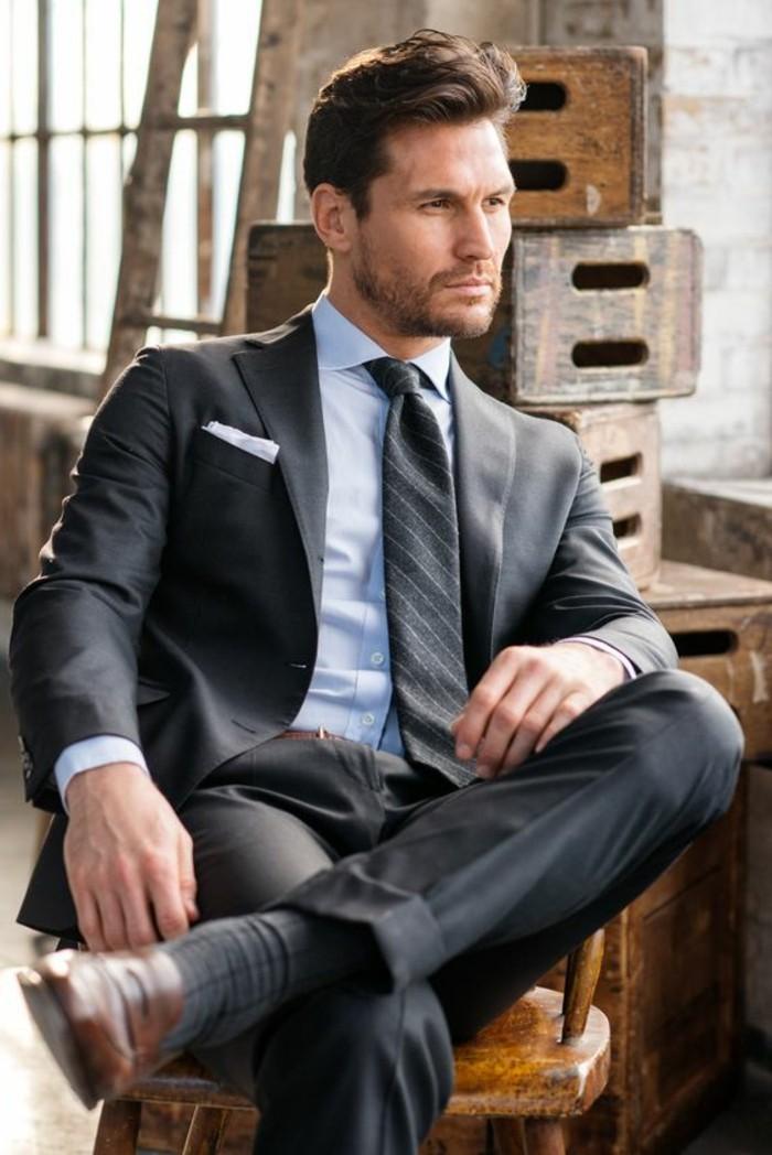 sitting brunette man, wearing pale blue shirt, dark grey two piece suit, striped dark grey tie, black tie attire for men, smart brown shoes
