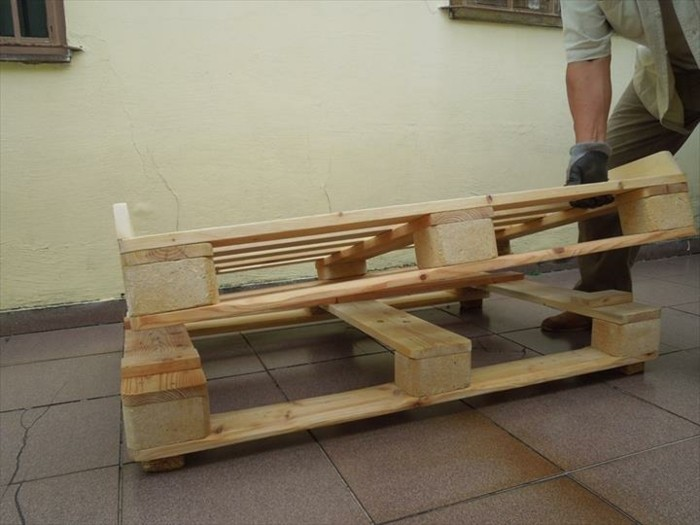man ing grayish clothing, putting half of a wooden pallet, on top of a whole pallet, how to make pallet furniture