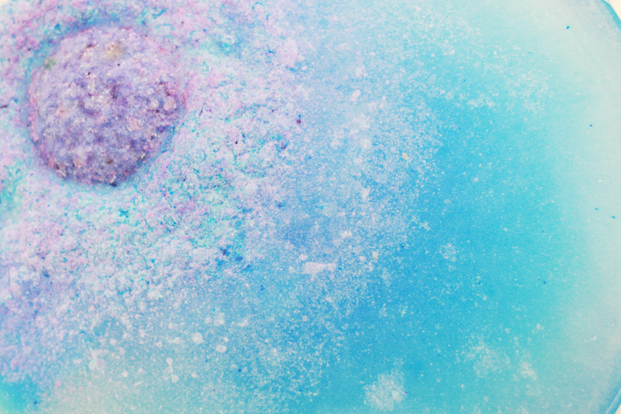 dissolving light purple bath bomb, melting in blue water, how to use a bath bomb, pale pink and white