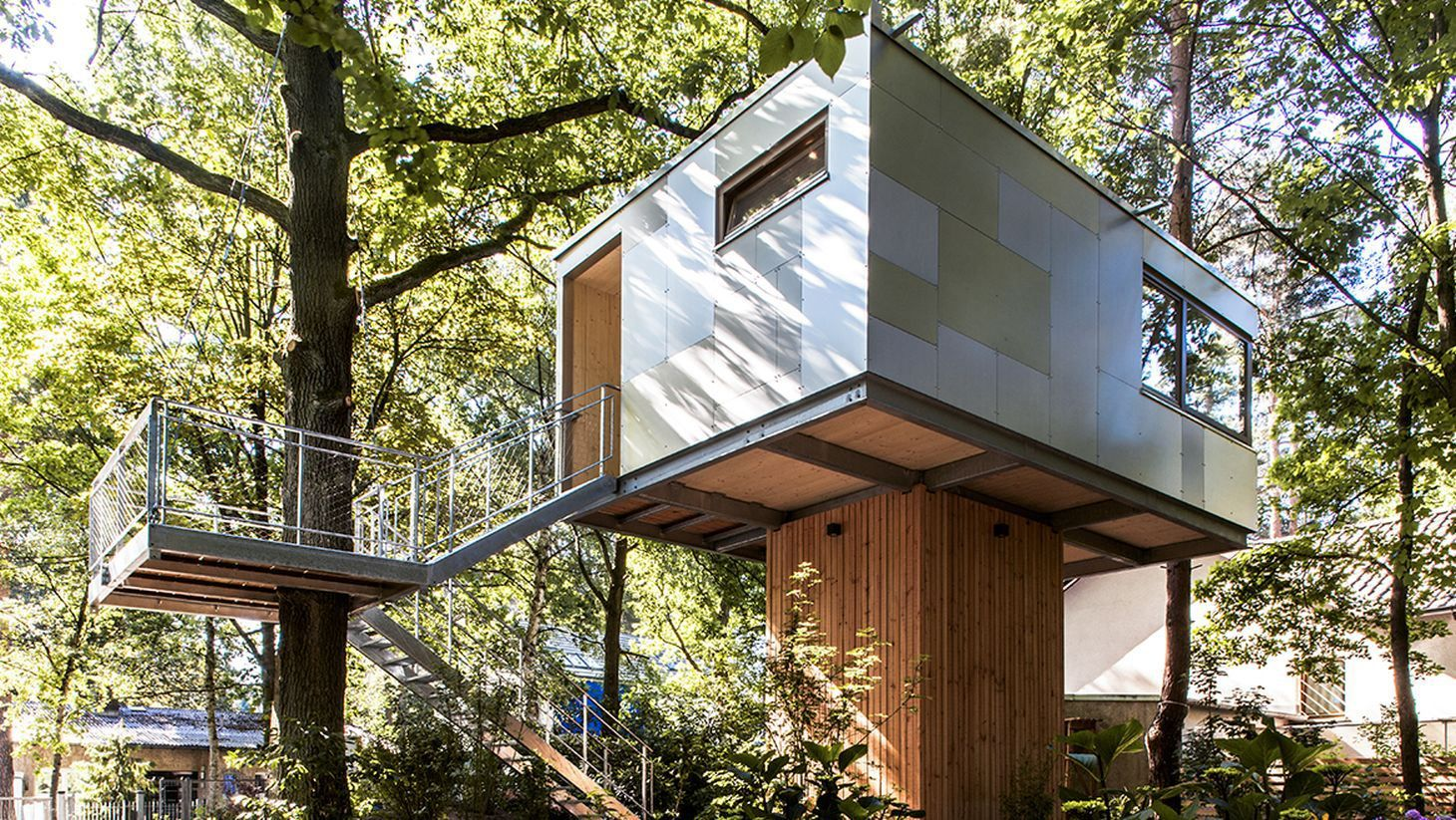 tile-covered industrial-style treehouse, suspended on a wooden platform, two windows and a door, accessible through a staircase, built around a nearby tree