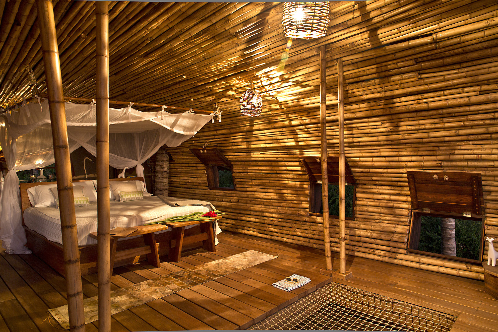 diy treehouse made from bamboo and wood, double bed with a baldachin, several lit lamps, three windows with open shutters