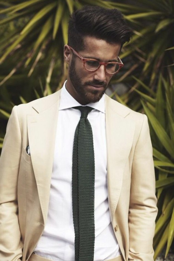 palm leaves behind a brunette man, with red-framed sunglasses, what is cocktail attire for men, ivory colored blazer, over white shirt with a dark tie