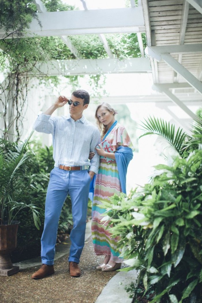 blue trousers and pale blue shirt, worn with brown shoes and sunglasses, by brunette man, standing next to blonde woman, in striped multicolored maxi dress, dressy casual men