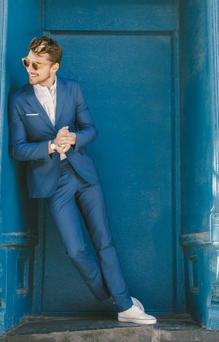 happy looking man, leaning on a blue wall, wearing a blue two piece suit, white shirt and white sneakers, mens summer wedding attire, sunglasses with yellow frames