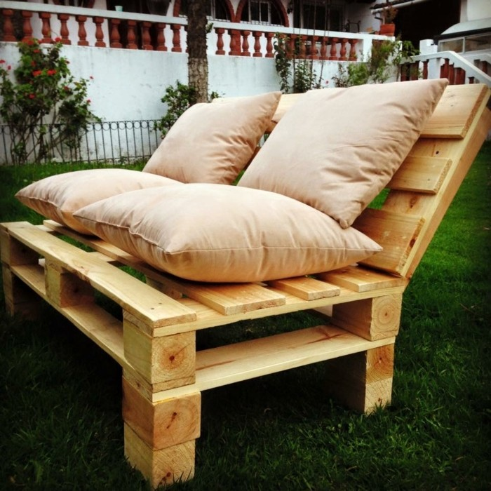 garden with green grass, and a light wooden bench, made from pallets, with several beige cushions on top, pallet outdoor furniture