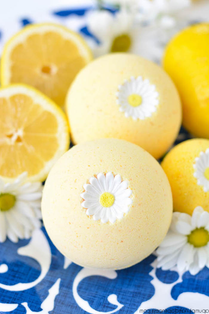 yellow bath bombs, decorated with daisies, what is a bath bomb, placed on white and blue cloth, near halved lemons and fresh daisies