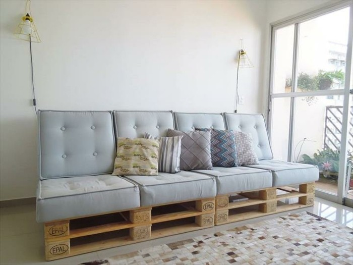 pale duck's egg blue pillows, covering a sofa made of pallets, with several cushions in different patterns, large window nearby