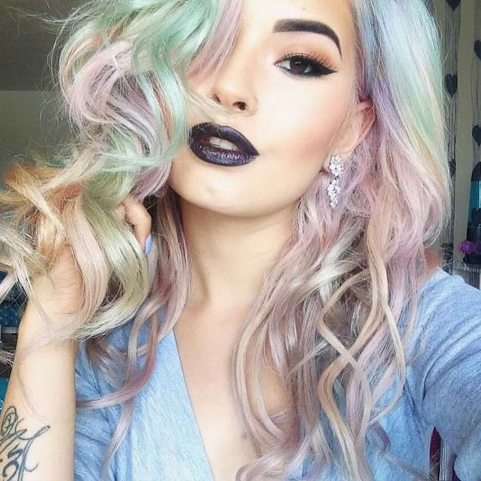 pastel green pink and yellow hair, slightly curled and worn by young woman, with black lipstick, fake eyelashes, and black eyeliner