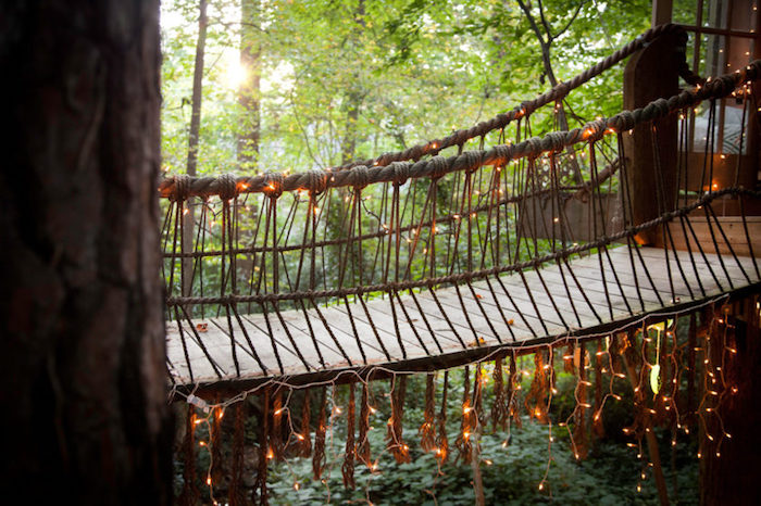 close up of a bridge, made from wooden planks and rope, treehouse designs, decorated with fairy lights, connecting two tree houses