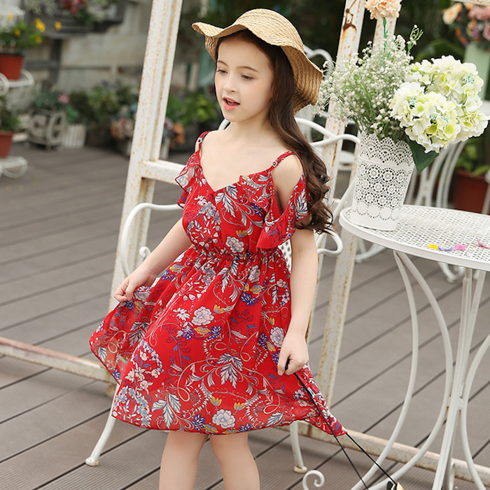 straw hat in pale beige, and floaty red sundress, with floral details and frills, worn by little girl, with long brunette hair