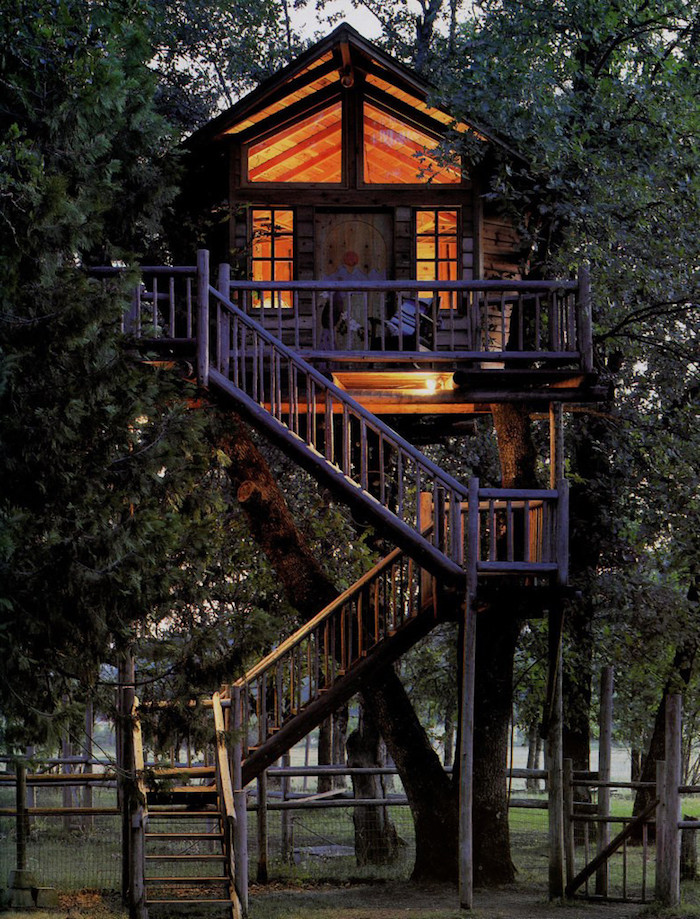 high above the ground, a tree house with several windows, illuminated from lamps inside, accessible through three sets of stairs