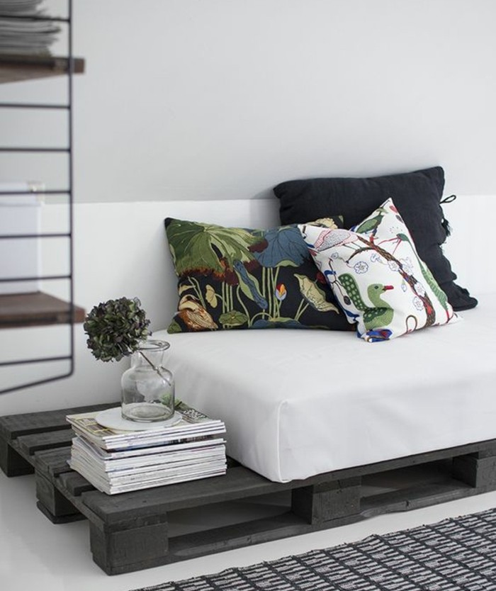 flower in a small glass vase, placed on top of a stack of magazines, black pallet diy sofa, with a white mattress, and three cushions