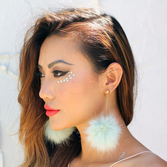 fluffy pale blue earrings, worn by brunette woman, with auburn strands in her hair, black eyeliner and bright, neon red lipstick, silver pearl stickers under here eye