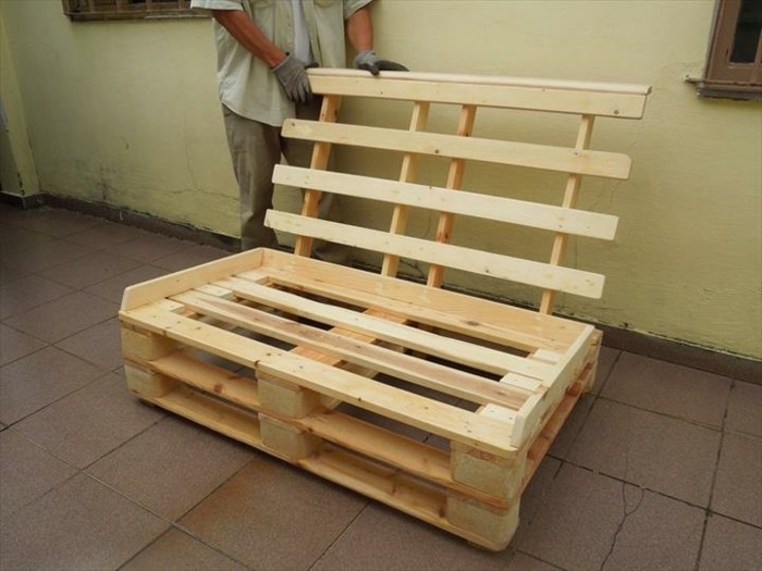 how to make pallet furniture, man in grey clothes, adding a wooden backrest, to a settee made from light wooden pallets