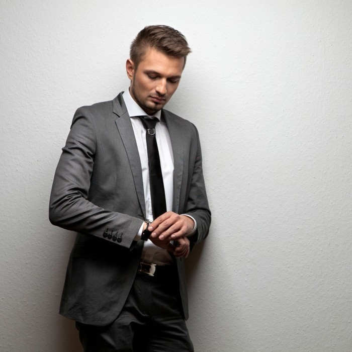 pewter gray two piece suit, black tie attire for men, worn by a young brunette man, with black tie, and a white shirt, looking at his watch