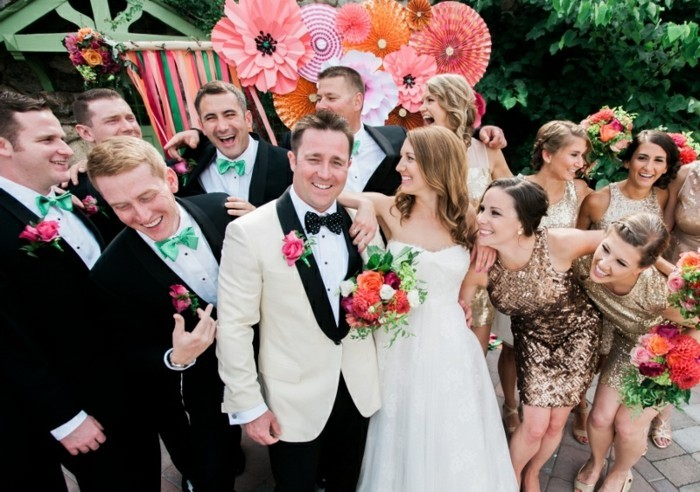 smiling bride and groom, surrounded by several men, dressed in black suits, with white shirts, and mint green bowties, mens summer wedding attire, bridesmaids dressed in golden sequin dresses