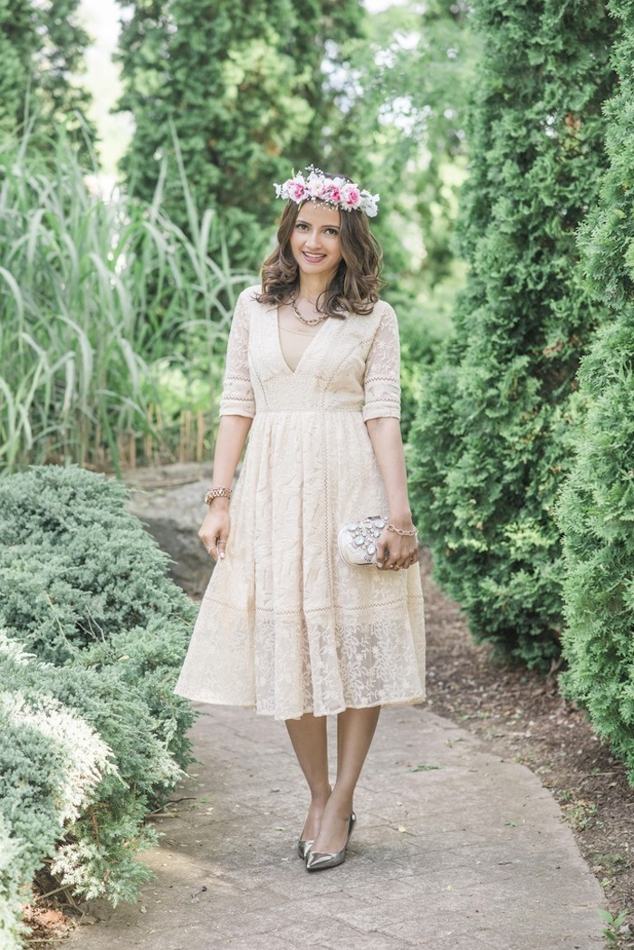 lace midi dress in cream, with 3/4 sleeves, worn with silver shoes, and a flower crown, by smiling brunette woman, holding a clutch bag, dressy casual