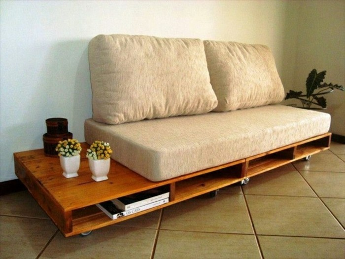 retro style diy sofa, made from polished wooden pallets, in a warm brown tone, with wheels and storage spaces, beige sofa cushions, and potted plants