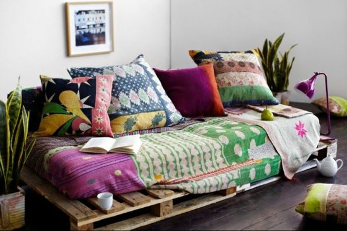 boho-style pallet sofa, covered in different textiles and cushions, in various colors and patterns, two potted plants nearby