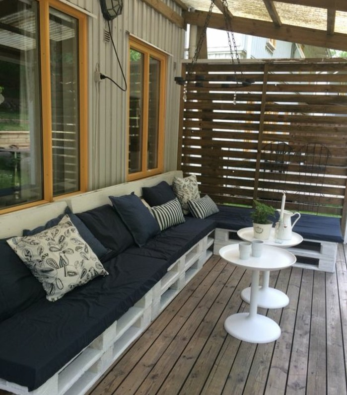 pallet outdoor furniture, terrace or porch bench, made from wooden pallets, painted in white, and covered with black foam pillows