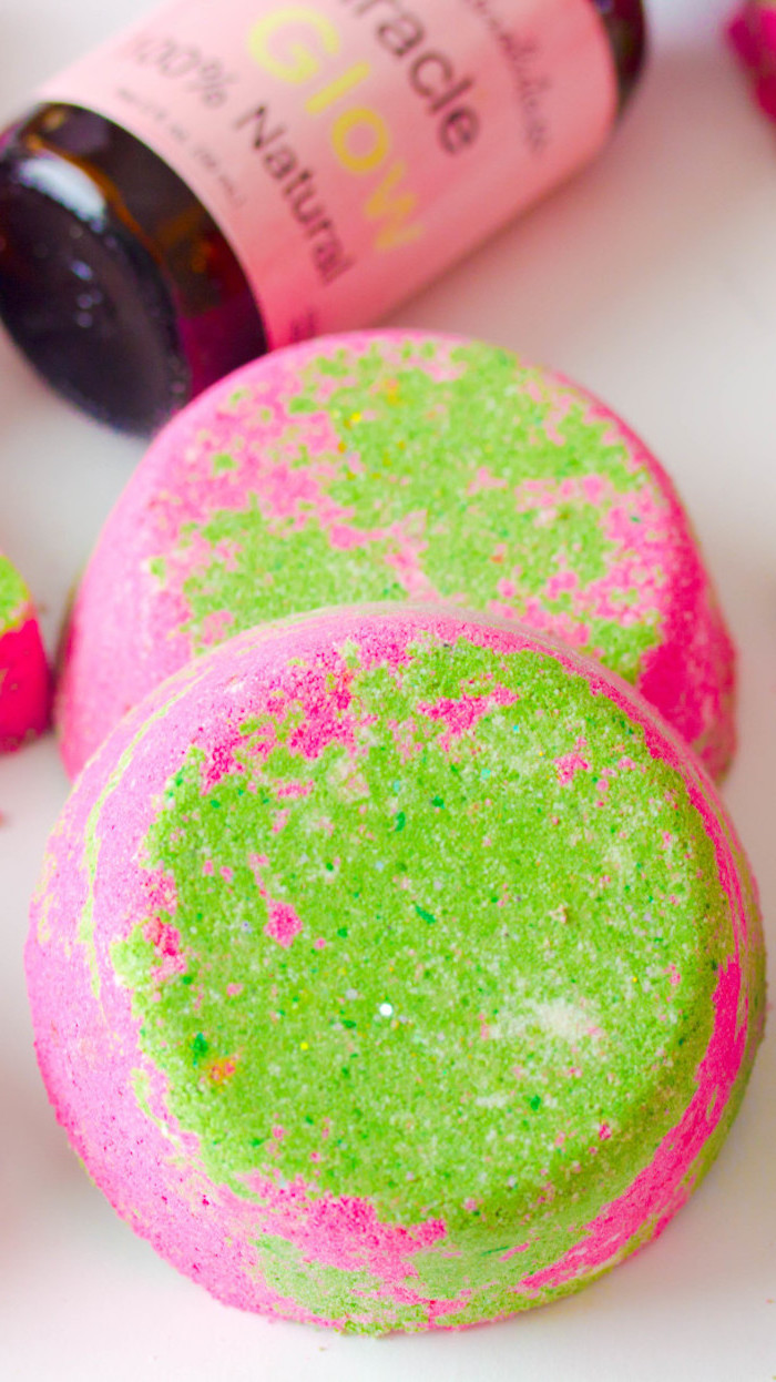 acid green and hot pink bath bombs, shaped like large round tablets, a set of two, placed on a white surface, near a bottle with pink label