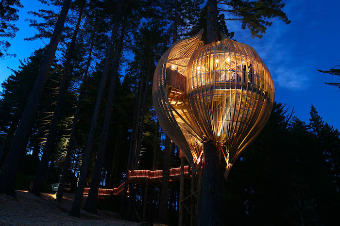 hot air balloon-shaped adult treehouse, made from wood and glass, and illuminated from within, with long staircase, dark nighttime forest