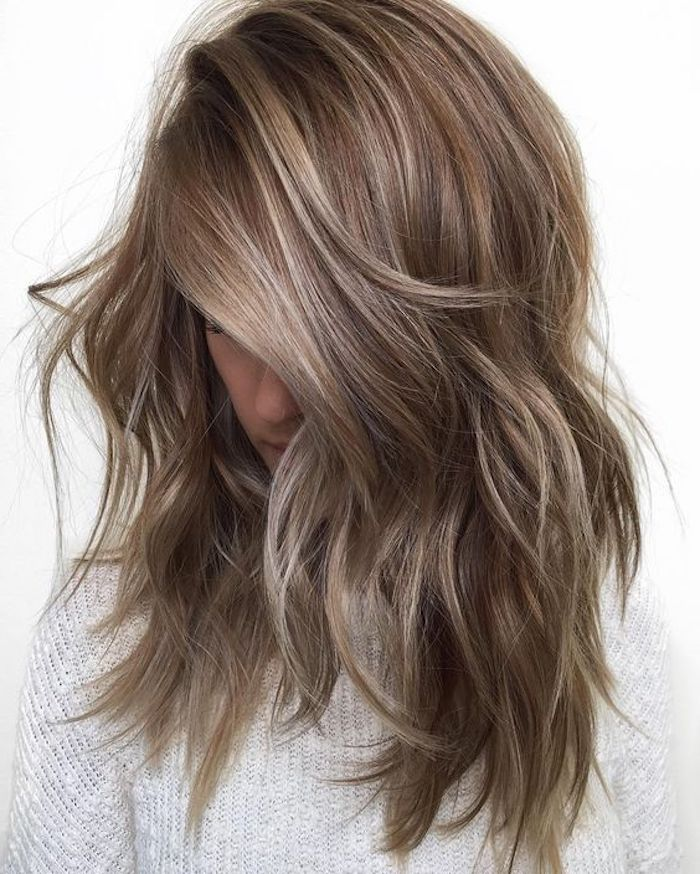 medium brown hair, layered and messy, falling over a young girl's face and hiding it, with ash blonde highlights