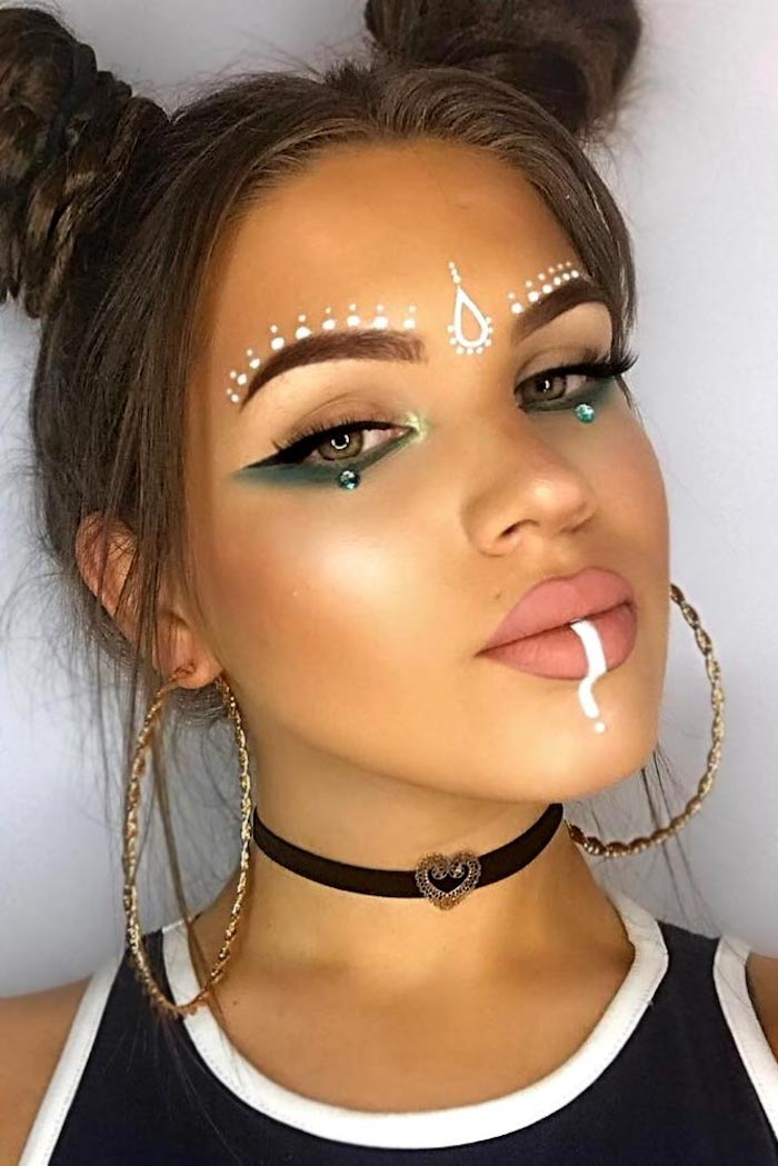 patterns done in white face paint, decorating the lips and forehead of a young girl, wearing turquoise eyeshadow, black eyeliner and nude pink matte lipstick