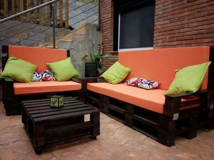 settee and sofa, made from dark wooden pallets, decorated with orange foam pillows, pallet patio furniture, light green and pink and white cushions
