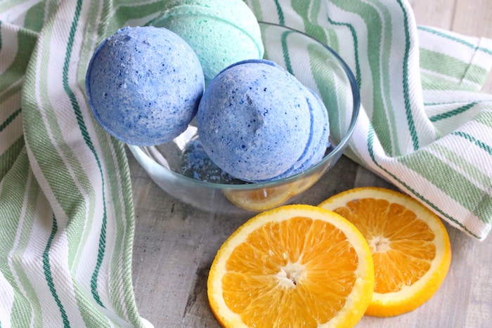 two orange slices, placed on a green and white striped table cloth, near clear glas bowl, containing two blue, and one turquoise bath bombs, how to make bath bombs