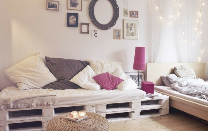 fairy lights and picture frames, decorating a room with a bed and white curtains, containing a large sofa, made of pallets, and covered with cushions