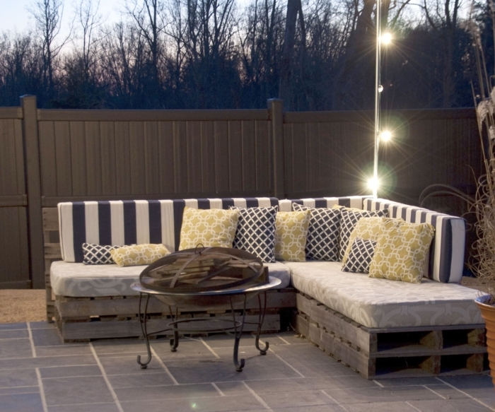 fairy lights hanging near a corner pallet settee, with soft striped backrests, and cushions with mustard, black and patterns, pallet outdoor furniture, wrought iron table