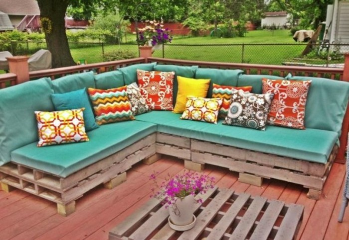 corner sofa made from pallets, covered with turquoise foam mattresses, and decorated with a selection of multicolored, patterned cushions in different sizes