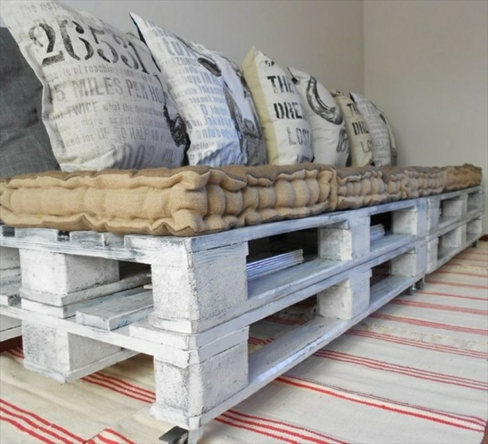 close up of a pallet sofa, made from several wooden pallets, painted in whitewash, how to make pallet furniture, beige mattress and several light grey pillows, with graphic print