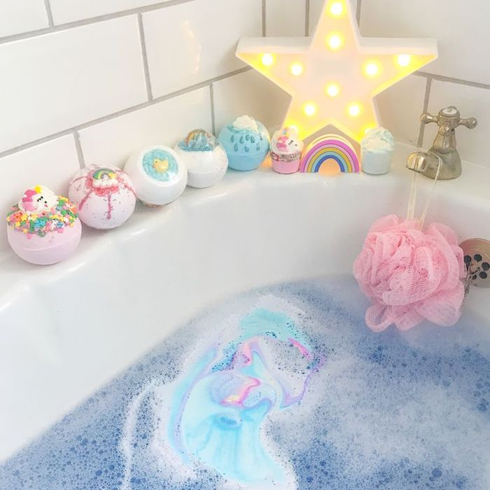 how to make bath bombs, pastel-colored bath bombs, placed on a white bathtub, containing a dissolving bath bomb, and blue water with white foam