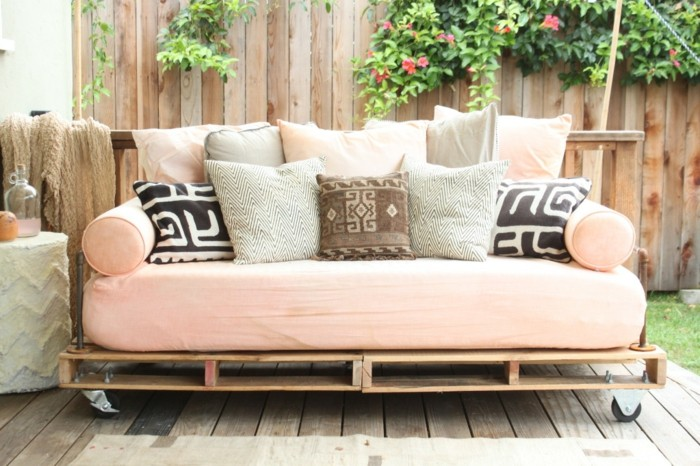 light pink mattress, covering a couch made of wooden pallets, decorated with lots of cushions, in pink and grey, black and white, brown and beige