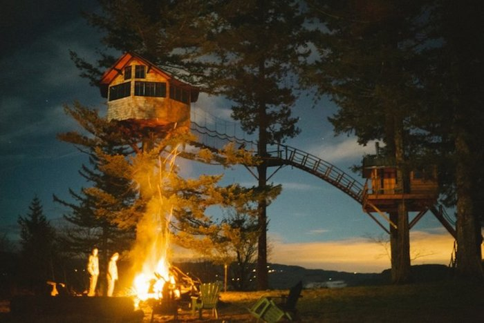 bonfire near two people, two tree houses built on large fir trees, and linked through a long bridge, photo taken at dusk