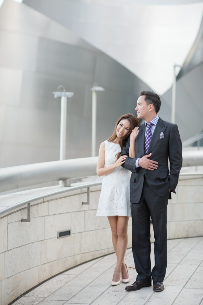 brunette east asian woman, wearing short white dress, standing hand in hand, with a man in a dark grey suit, mens summer wedding attire, wearing purple patterned tie